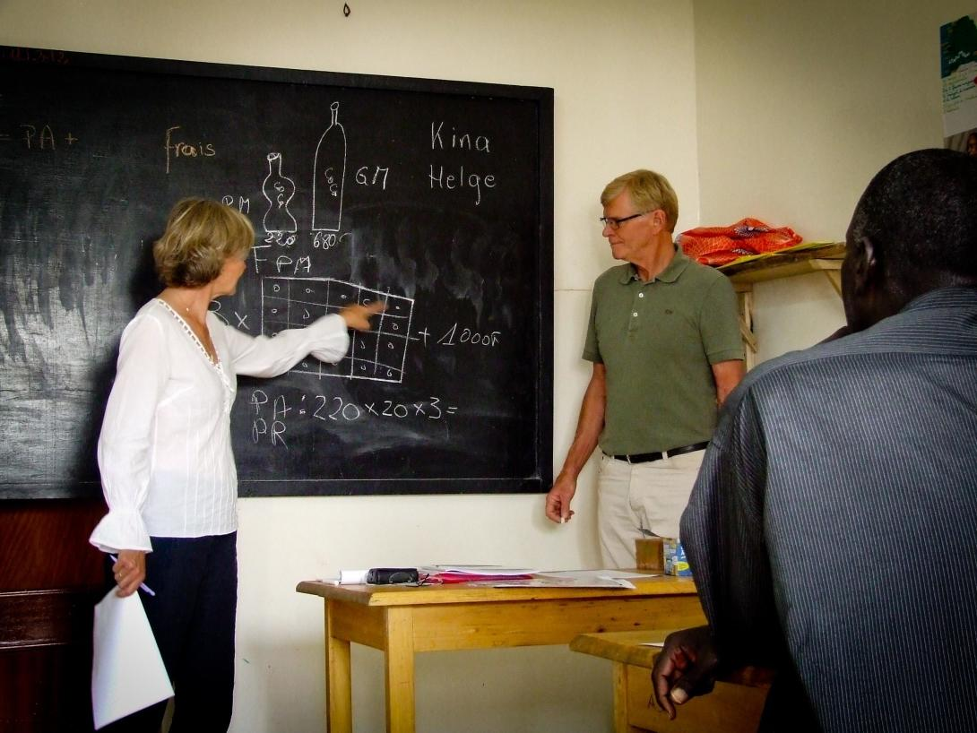 A female and male volunteer teaching in a micro finance project in Tanzania.